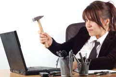 Angry woman #8. Businesswoman at desk with laptop and hammer on white background Royalty Free Stock Image