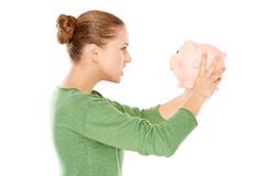 Angry woman arguing with her piggy bank Royalty Free Stock Photo
