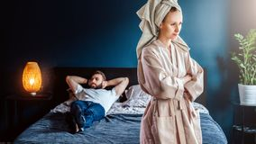 Angry woman in bathrobe stands in bedroom,her arms crossed over chest. Man is lying on bed .Couple having problems. royalty free stock photo