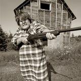 Angry woman with big gun stock image