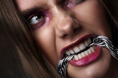 Angry Woman bite a Chain. Expressive beauty Look Stock Photo