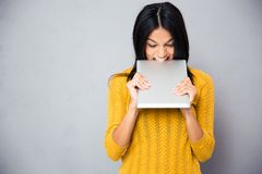 Angry woman biting tablet computer Royalty Free Stock Photo