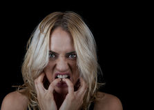 Angry Woman on Black Background. Angry and frustrated young woman biting her nails on a black background with room for text Royalty Free Stock Photography
