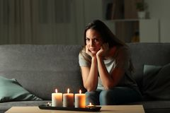 Angry woman during a blakout at home. Angry woman looking at camera during a blakout sitting on a couch in the living room at home Stock Images