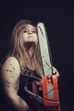 Angry woman. Bloody maniac woman with chainsaw stands in empty dark room royalty free stock photos