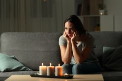 Angry woman boring during a blackout in the night. Sitting on a couch in the living room at home Royalty Free Stock Photo