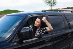 Angry woman in a car. The woman is cussing on someone and holding car wheel with one hand of a black car Royalty Free Stock Photography