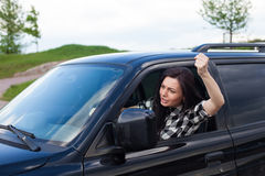 Angry woman in a car. The woman is cussing on someone and holding car wheel with one hand and showing a fist of a black car Stock Photography