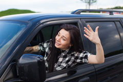 Angry woman in a car. The woman is cussing on someone and holding car wheel with one hand with tattoo of a black car Royalty Free Stock Photos