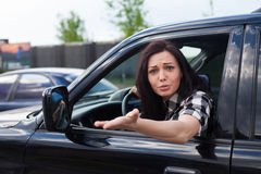 Angry woman in a car. The woman in white-black shirt is cussing on someone and holding car wheel with one hand of a black car Royalty Free Stock Photos