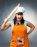 Angry woman cook. Applying rolling pin to her head Stock Image