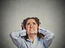 Angry woman covering ears looking up stop loud noise. Closeup portrait young angry unhappy stressed woman covering her ears looking up stop making loud noise it' Royalty Free Stock Photo