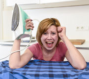 Angry woman or crazy busy housewife ironing shirt lazy at home k Stock Photo