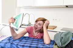 Angry woman or crazy busy housewife ironing shirt lazy at home k Royalty Free Stock Photo