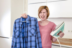 Angry woman or crazy busy housewife ironing shirt lazy at home k Royalty Free Stock Photography