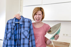 Angry woman or crazy busy housewife ironing shirt lazy at home k Stock Photos
