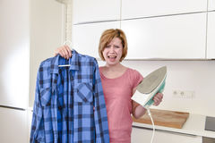 Angry woman or crazy busy housewife ironing shirt lazy at home k Stock Image