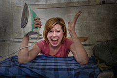 Angry woman or crazy busy housewife ironing shirt lazy at home kitchen using iron Royalty Free Stock Images