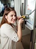 Angry woman cutting chain on refrigerator with cutters Stock Photos