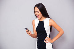 Angry woman in dress shouting on smartphone. Over gray background Stock Images