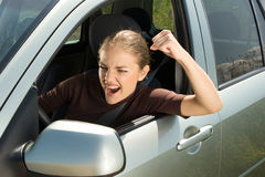 Angry woman driver. Young woman driver yelling and  shaking her fist out car window Royalty Free Stock Image