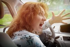 Angry woman driver screaming while driving a car. Angry woman driver screaming and gesturing while driving a car. Negative human emotions concept Stock Photos
