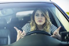 Angry woman driving a car. The girl with an expression of displeasure is actively gesticulating behind the wheel of the car stock photos