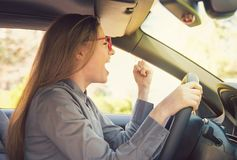 Angry woman driving car in rage stock photos
