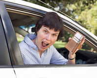 Angry Woman, Empty Wallet. A middle-aged woman sitting in her car looks very upset as she finds her wallet missing credit cards and money stock photo