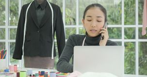Angry woman fashion designer sitting at her desk talking on the phone stock footage