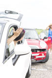 Angry woman gesturing while talking to female crashing car on road Royalty Free Stock Images