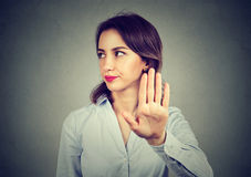 Angry woman giving talk to hand gesture. With palm outward  gray wall background. Negative human emotion body language Stock Image