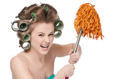 Angry woman in hair rollers is holding swab. Angry crazy housewife in hair rollers is holding swab Stock Image