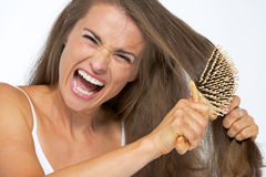 Angry woman having hard time combing hair Stock Images