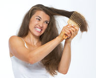 Angry woman having hard time combing hair Stock Photos