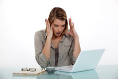 Angry woman at her desk Stock Images