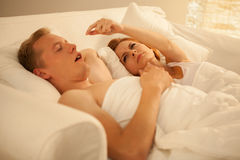 Angry woman and her snoring husband. Angry women and her snoring husband lying in bed Royalty Free Stock Image