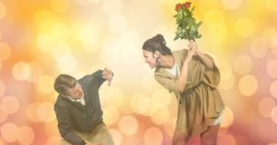 Angry woman hitting man with flowers over blur background Royalty Free Stock Photos