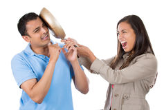 Angry woman hitting man on the head with frying pan Royalty Free Stock Photos