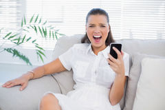 Angry woman holding her phone screaming at camera. In bright living room Stock Photo