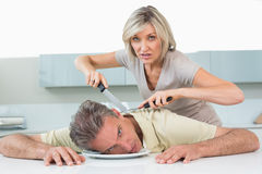 Angry Woman Holding Knife To Mans Neck In Kitchen Stock Image