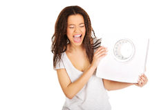 Angry woman holding a scale. Royalty Free Stock Images