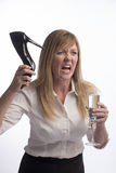 Angry woman holding stiletto shoe Royalty Free Stock Photography