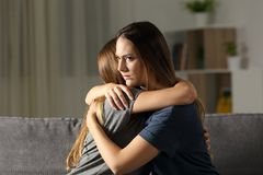 Angry woman hugging a friend at home. Angry women hugging a friend sitting on a couch in the living room at home stock photography