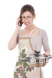 Angry woman in the kichen holding pot altercating over phone Stock Photo