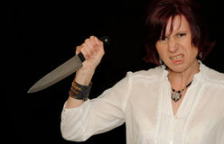 Angry woman with knife. An angry woman holding a sharp knife, black background studio image stock images