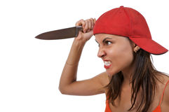 Angry woman with knife. An isolated profile of an angry young woman wearing a red baseball cap backwards, holding a large knife as if to attack stock image