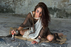 Angry woman with knife. Dangerous woman in rags sitting in a derelict building with a bloody knife Stock Photography