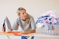 Free Angry Woman Looking At Pile Of Clothes At Ironing Desk Stock Photography - 136499752