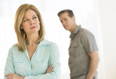 Angry Woman Looking Away With Man In Background At Home Royalty Free Stock Images